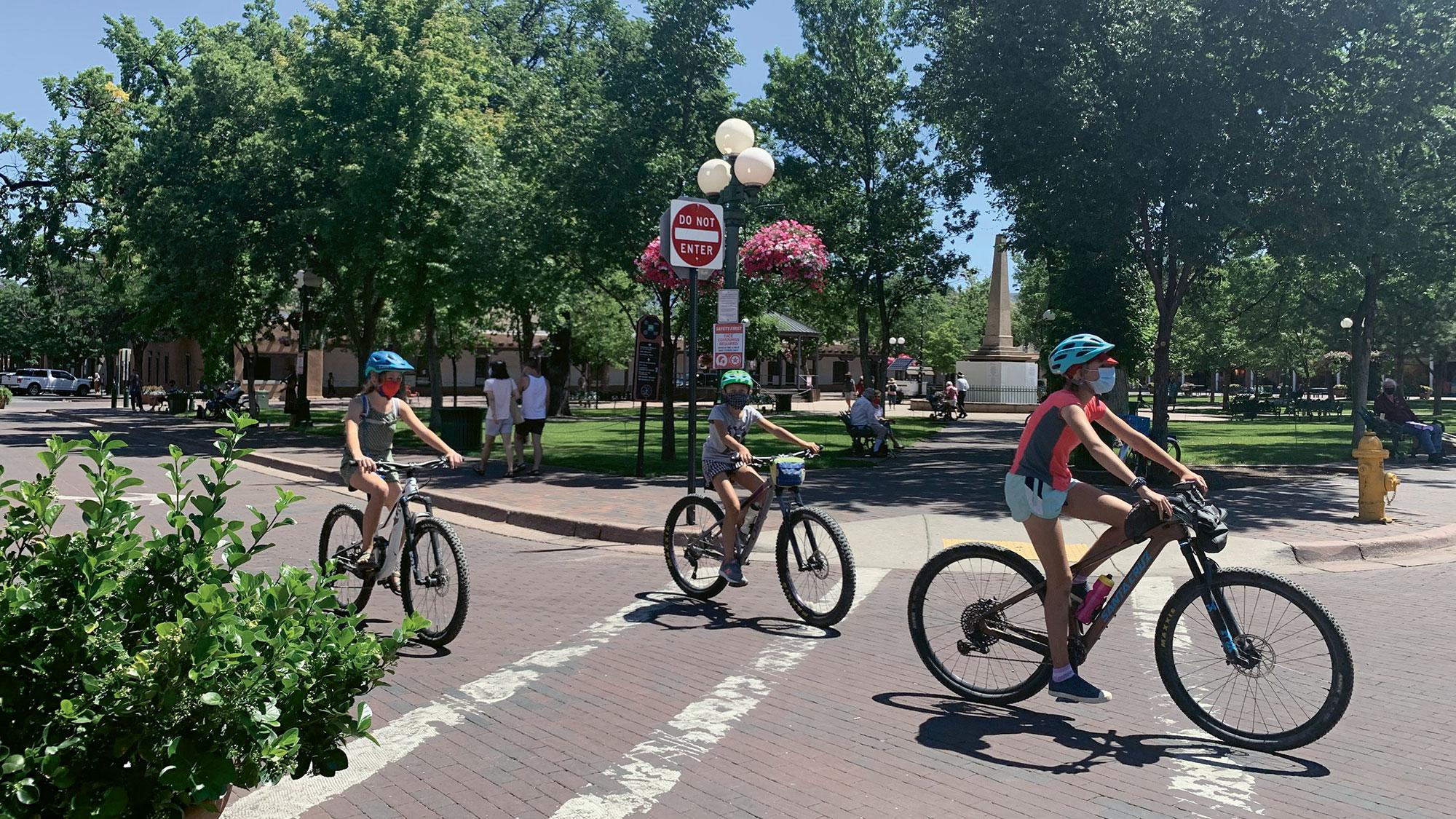 Os ciclistas circulam uma praça em grande parte vazia em Santa Fe, que normalmente está cheia de turistas no verão.